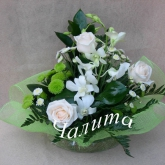 An arrangement on a floral foam of roses, orchids and other flowers and assorted greenery. Price: 34 USD