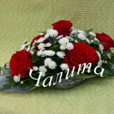 An arrangement of an oblong form of roses, chrysanthemum and greenery. Price: 32 USD