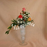 An arrangement of roses and other flowers on a loral foam. Price: 24 USD