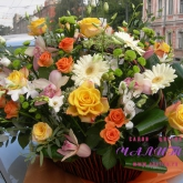 A gift basket in the shape of a boat filled with lots of flowers. Price: 254 USD