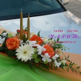 An arrangement with candles of roses, gerbera diasies, orchid and other flowers and greenery. Price: 68 USD