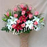 A gift basket of lilies and roses, decorated with assorted greenery and beads. Price: 83 USD