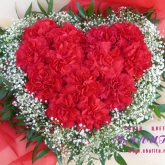 An arrangement in the shape of a heart of 13 carnations with baby's breath and ruskus. Price: 51 USD