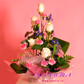 An arrangement of 5 white roses, irises, carnations and greenery. Price: 37 USD